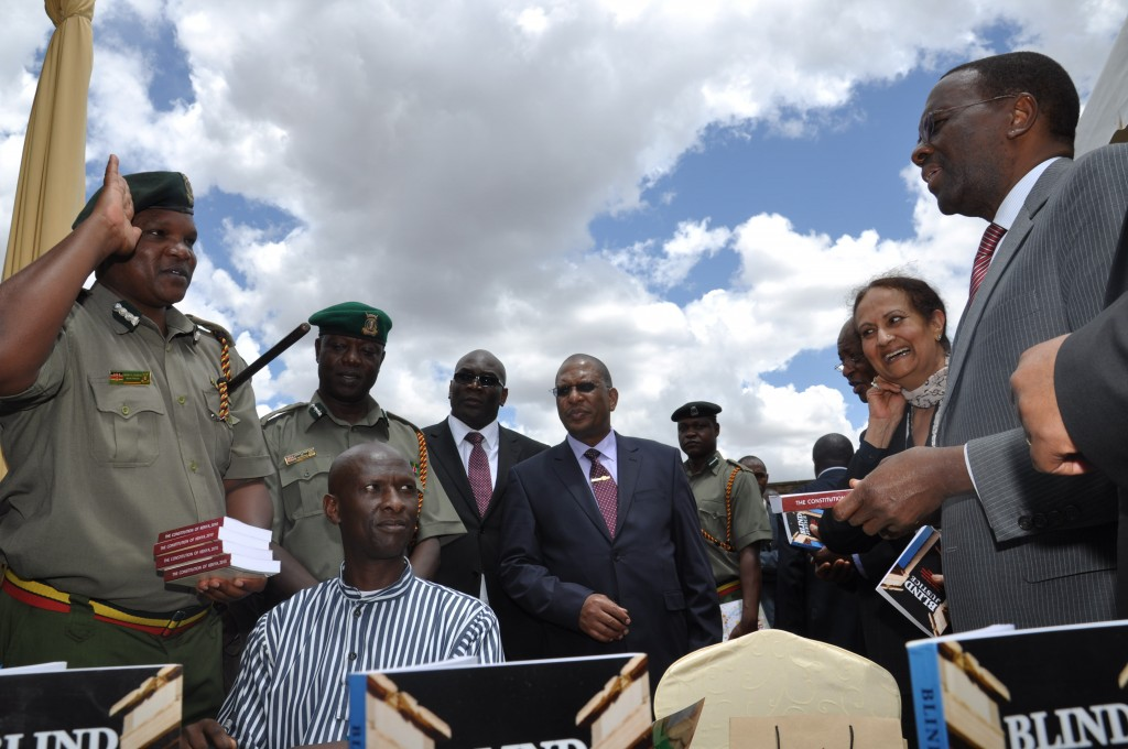 Chief Justice and Chairman of the Council for Law Reporting Dr. Willy Mutunga (right) flanked by the Deputy Chief Justice Kalpana Rawal (second right) hands over copies of the pocket-sized Constitution of Kenya, 2010 published by Kenya Law to officers at the Kamiti Maximum Prison during the Judicial Service Week on October 11, 2013. Looking on are the Commissioner of Prisons Mr. Isiah Ougo (second left); the Chief of Staff in the Office of the Chief Justice Mr. Duncan Okello (third left) and The Director of Public Prosecutions Mr. Keriako Tobiko (centre). Seated is Mr. Haron Thomas Nyandoro, an inmate at the prison who launched his book – Blind Justice: The True Story of an Innocent Man Sentenced to Hang, and his Untiring Quest for Justice.