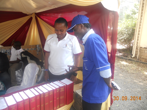 Kenya Law's Eva Murage chats with a Member of the public during Nairobi International Trade Fair held from 29th September  to  5th October 2014 at the Jamuhuri Park grounds.