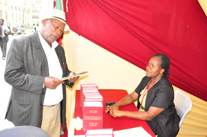 Kenya Law Marketing Assistant Ms. Caroline Wairimu(right) attends to a member of Public at during the Legal Aid week held at Milimani Law Court, on 27th October 2014.
