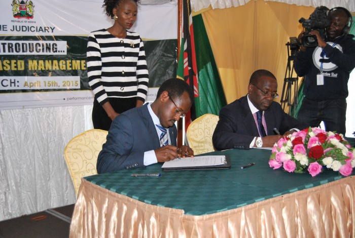 Kenya Law Ag. CEO/Editor Mr. Long'et Terer signs the performance management understanding agreement alongside the Chief Justice and President of the Supreme Court, Hon. Dr. Willy Mutunga, D.Jur, SC, EGH