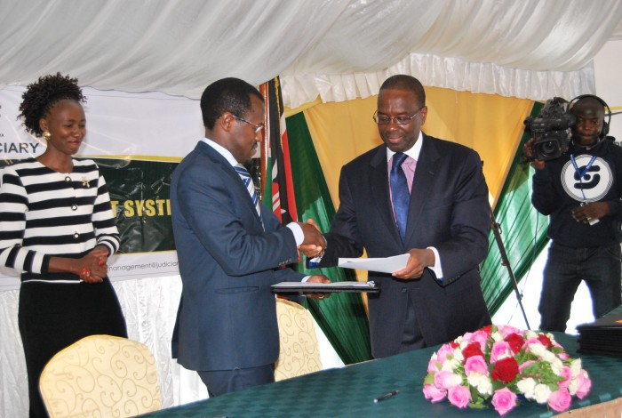 Mr. Long'et Terer (Ag. CEO/Editor, Kenya Law) receives the performance management understanding agreement from the Chief Justice and President of the Supreme Court, Hon. Dr. Willy Mutunga, D.Jur, SC, EGH.