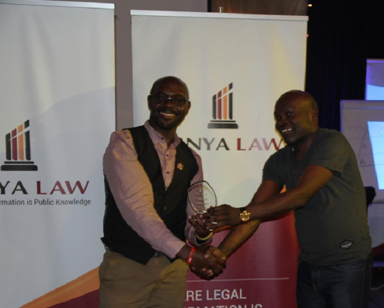 Former Kenya Law CEO/Editor Mr. Michael Murungi presents the 2016 -Team player of the Year, Law Reporting Department to Musa Okumu.