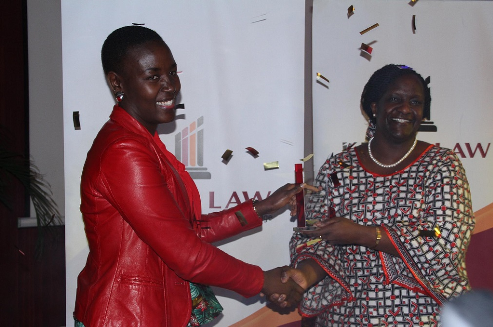Winnie Mbori of the H.R & Admin department  receives the Employee of the year -2016 award from Ms. Christine Agimba.