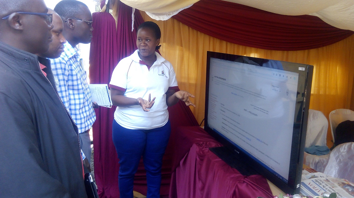 Ms. Carolyne Wairimu (right) educates the public on how to use the Kenya law website.