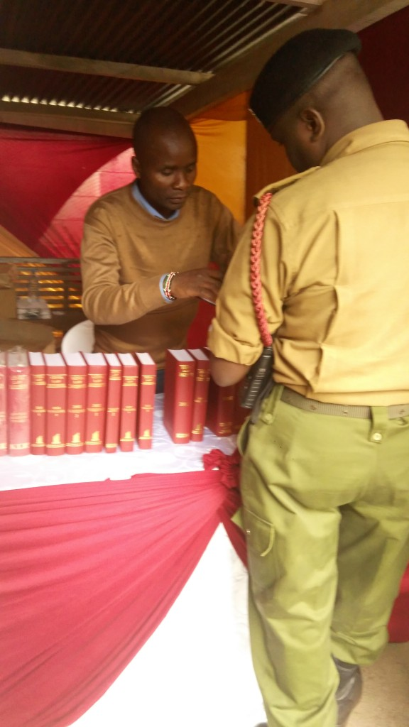 Kenya Law's  Jeremiah Wanga (left )assists a police officer at the Kenya Law stand during the Employment and Labour relations Court annual Open day on 19th May, 2017 at the Milimani Commercial  Court grounds.