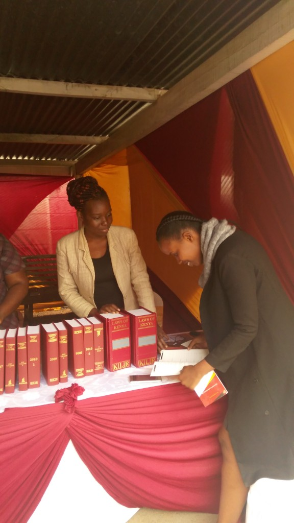 Kenya Law's  Nasike Robai (left )assists a member of the public at the Kenya Law stand during the Employment and Labour relations Court annual Open day on 19th May, 2017 at the Milimani Commercial  Court grounds.