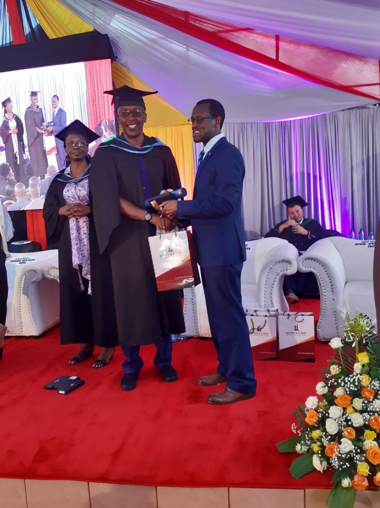 Kenya Law CEO/Editor, Mr. Long'et Terer presents one of the graduates with the gift pack.