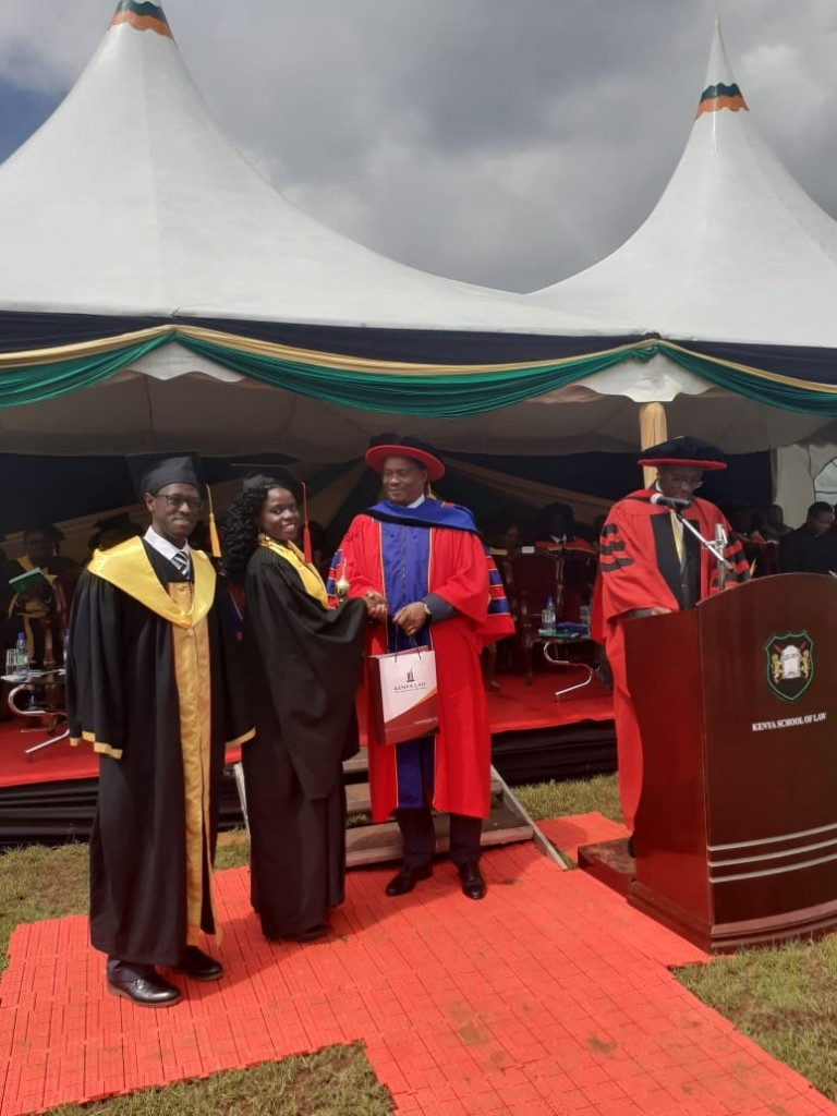 Kenya Law CEO, Mr. Long'et Terer and the Speaker of the National Assembly Hon. Justin Muturi present the Kenya Law gift to Ms. Ebomwbwe Margret Owade, the Overall best Student-Female.